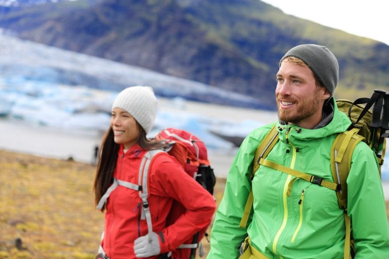 Hiking adventure travel people living active healthy lifestyle wearing jackets and backpacks on Iceland by glacier and glacial lagoon / lake of Fjallsarlon, Vatna glacier, Vatnajokull National Park.