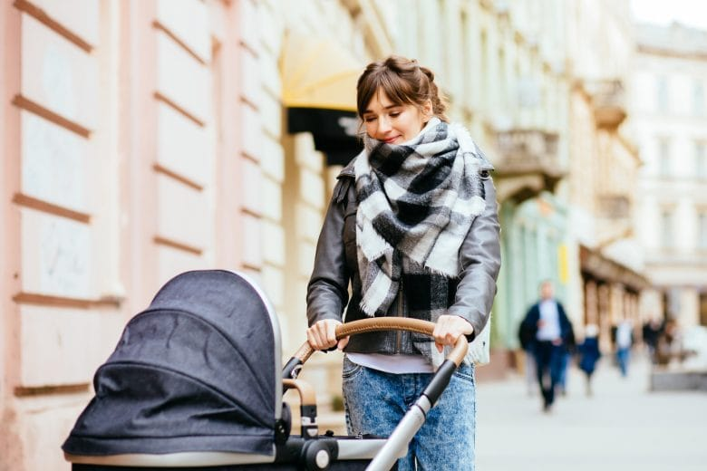 Young beautiful mother walking with baby carriage in european city center.