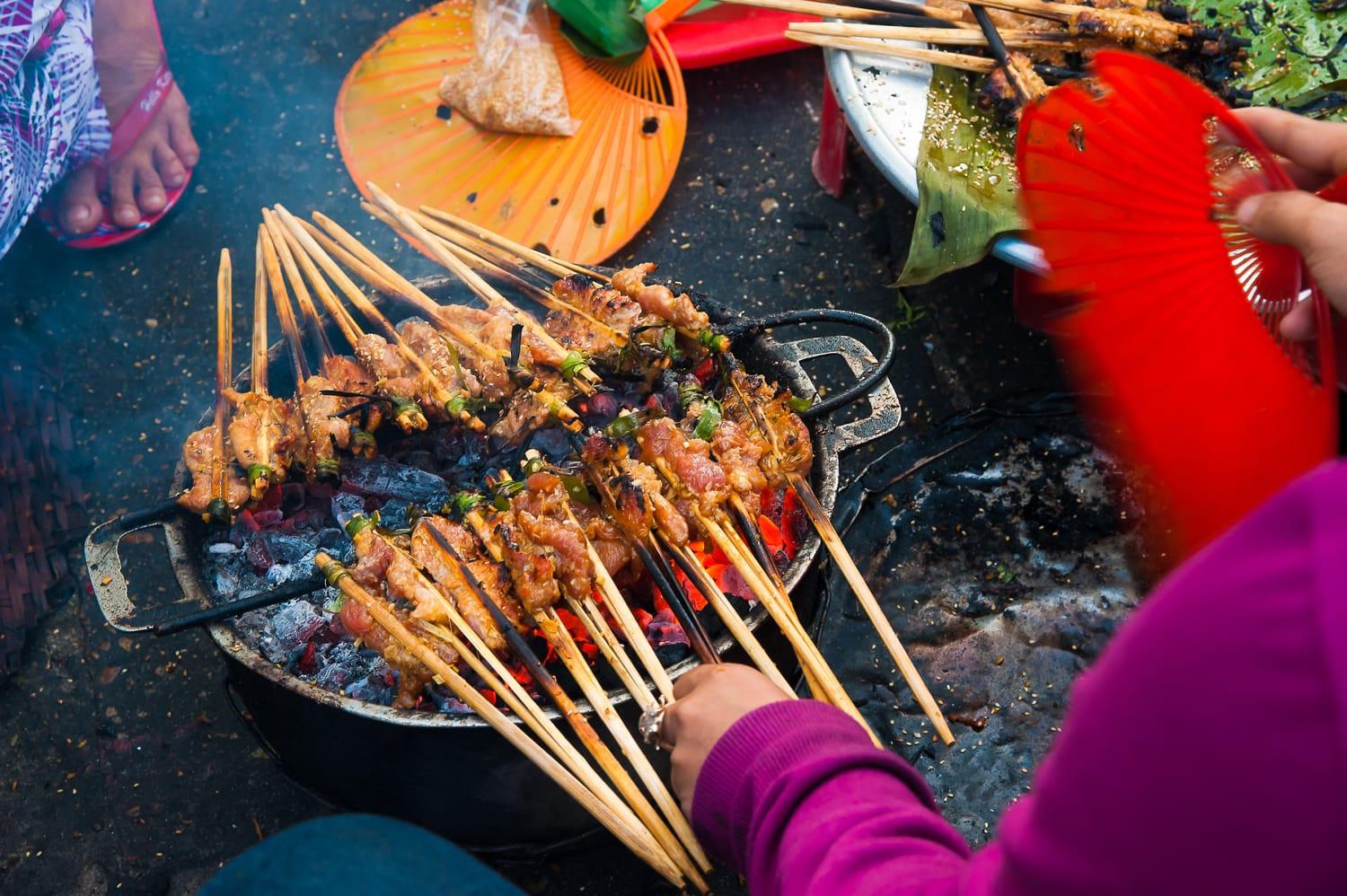 Hawker prepare the skewered grilled meats at street of Hoi An, a local delicacy of Vietnam