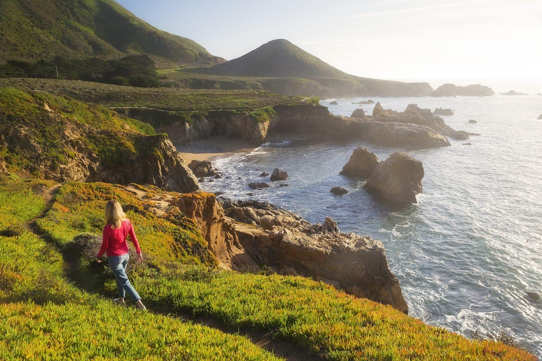 A female hiker walks down a trail in Big Sur, California.