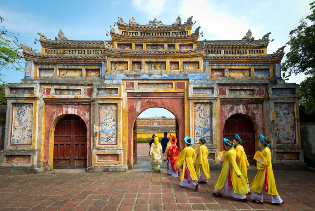People in traditional costumes walk under an archway in the Imperial City of Hue, Vietnam.