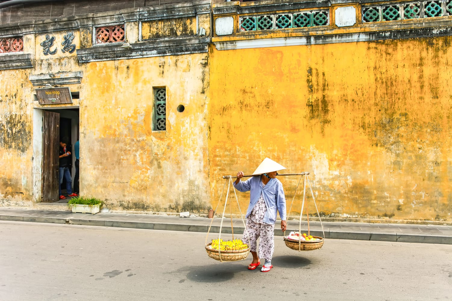 Vietnamese woman street seller In hoi an Vietnam in ancient town Hoi An with view of typical yellow houses