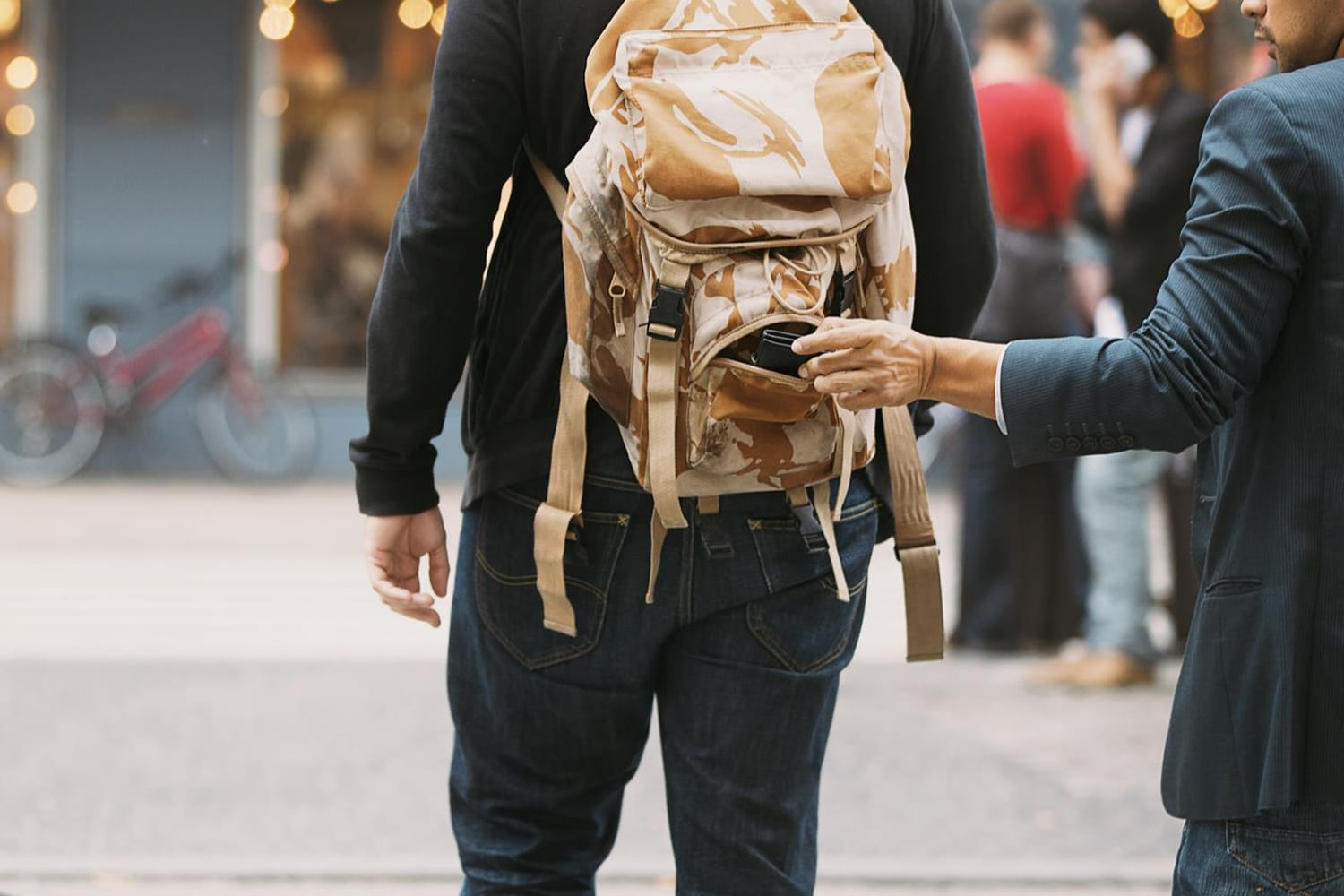 Thief stealing wallet from backpack of a man walking on street during daytime. Pickpocketing on the street during daytime