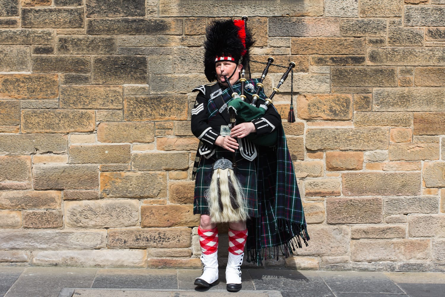 A bagpiper, a street musician wearing kilt and traditional scottish costume