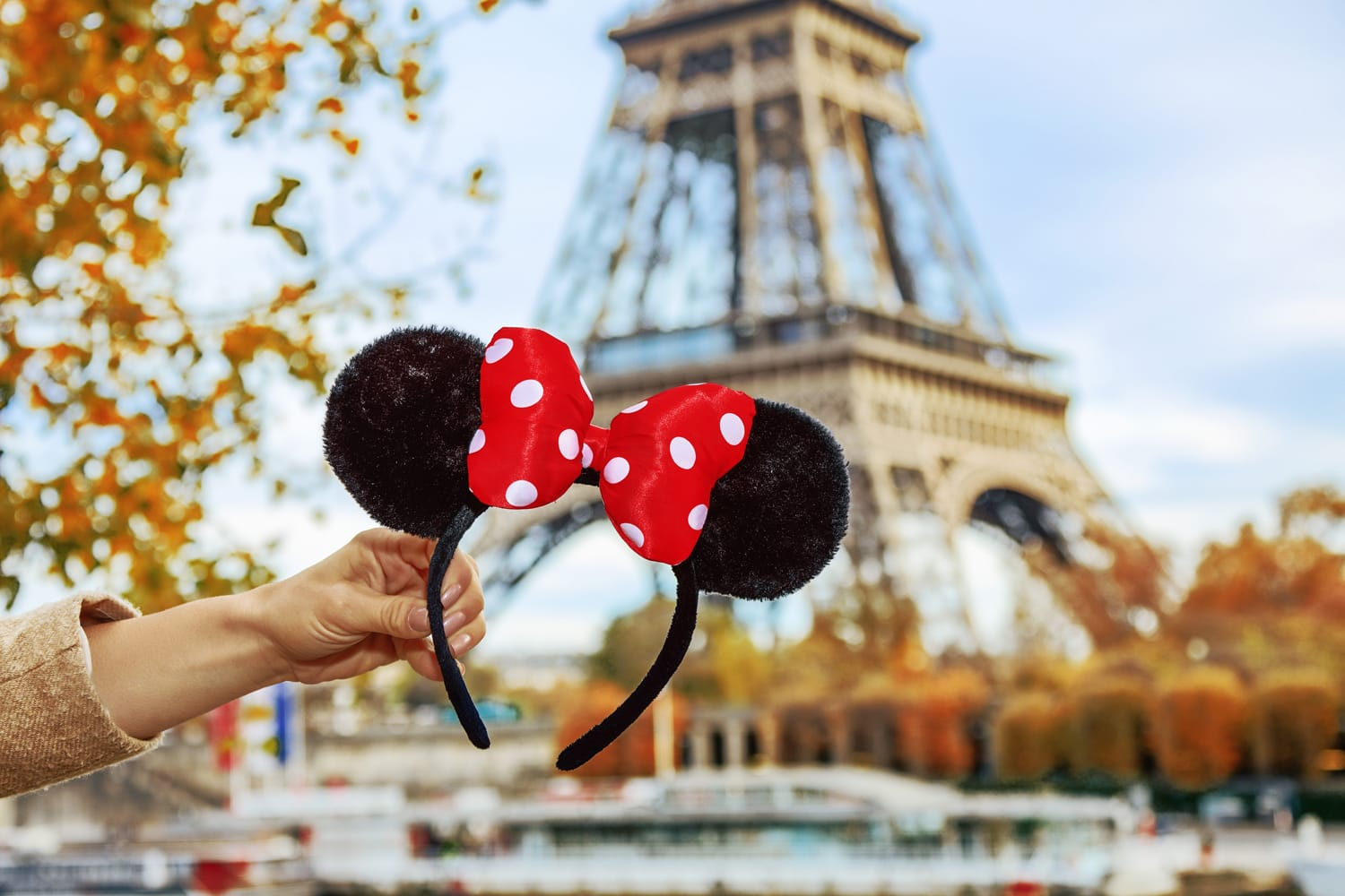 Closeup on Minnie Mouse Ears in female hand on embankment near Eiffel tower in Paris, France