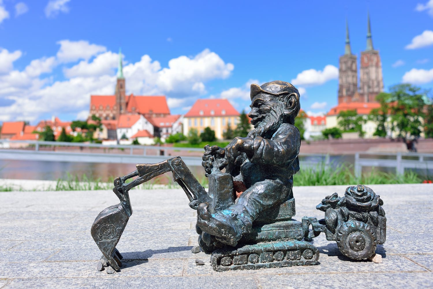 A small gnome sculpture in the background of the panorama of Wroclaw.