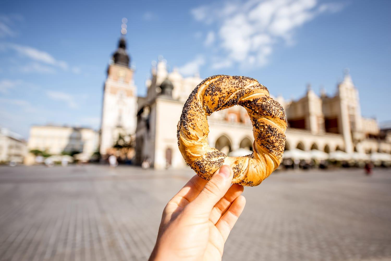 Holding prezel, traditional polish snack on the Market square in Krakow