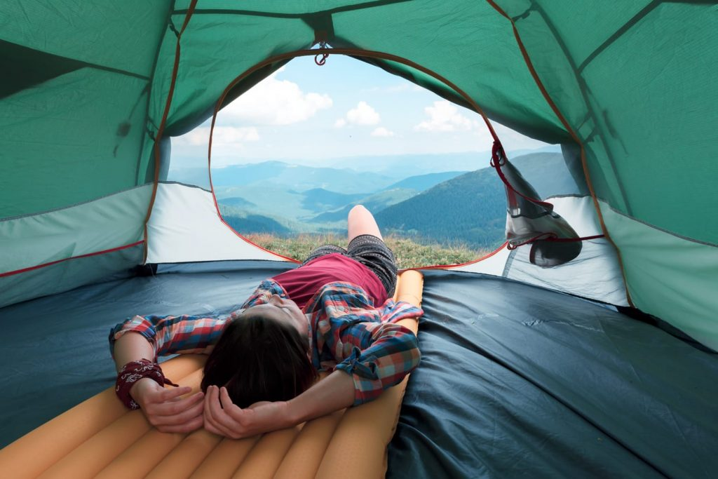 1df811ad36e Girl lies in they tent against the backdrop of an incredible mountain  landscape