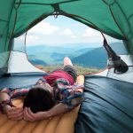 Girl lies in they tent against the backdrop of an incredible mountain landscape