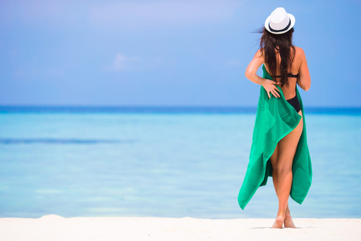 Young woman with green beach towel during tropical vacation