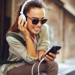 Young woman listening to music via headphones on the street