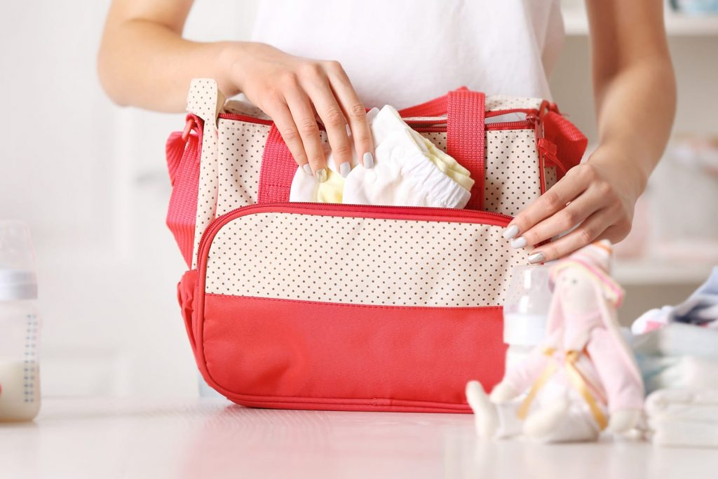 Woman packing a diaper bag backpack