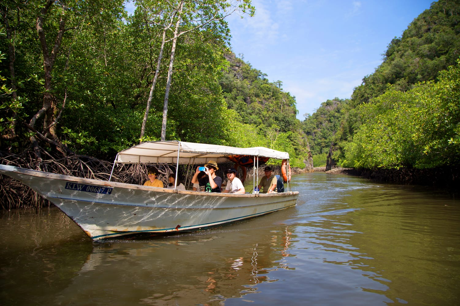 Tourists travel by boat at Kilim Karst Geoforest park in Langkawi, Malaysia