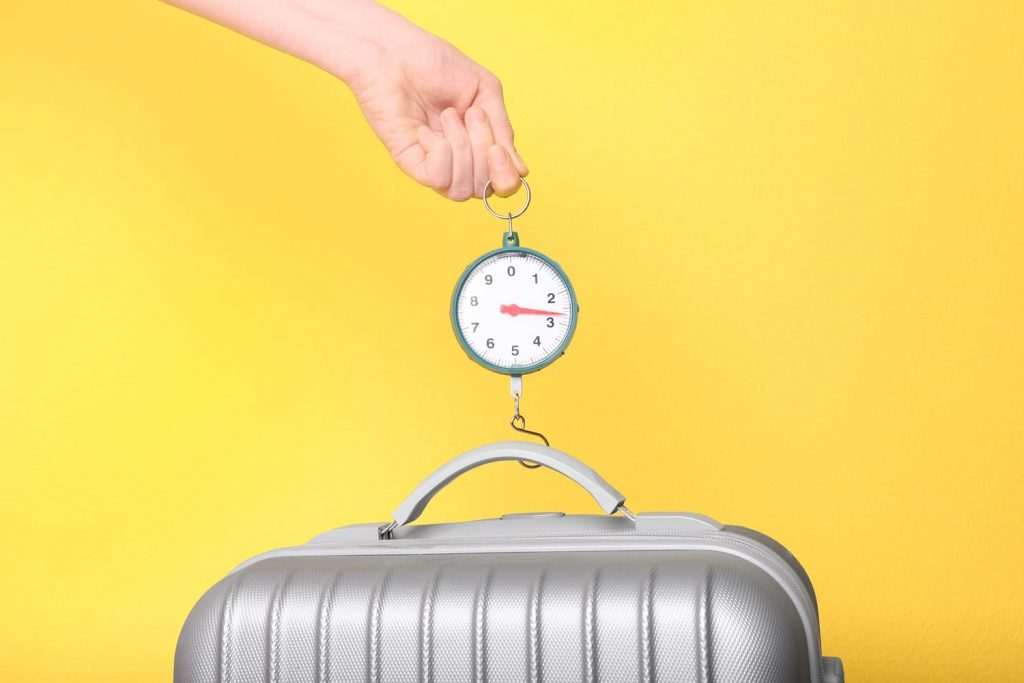Woman weighting heavy luggage