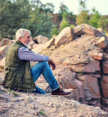 tourist with a gray beard and hair in jeans and a travel vest on the background of the gorge