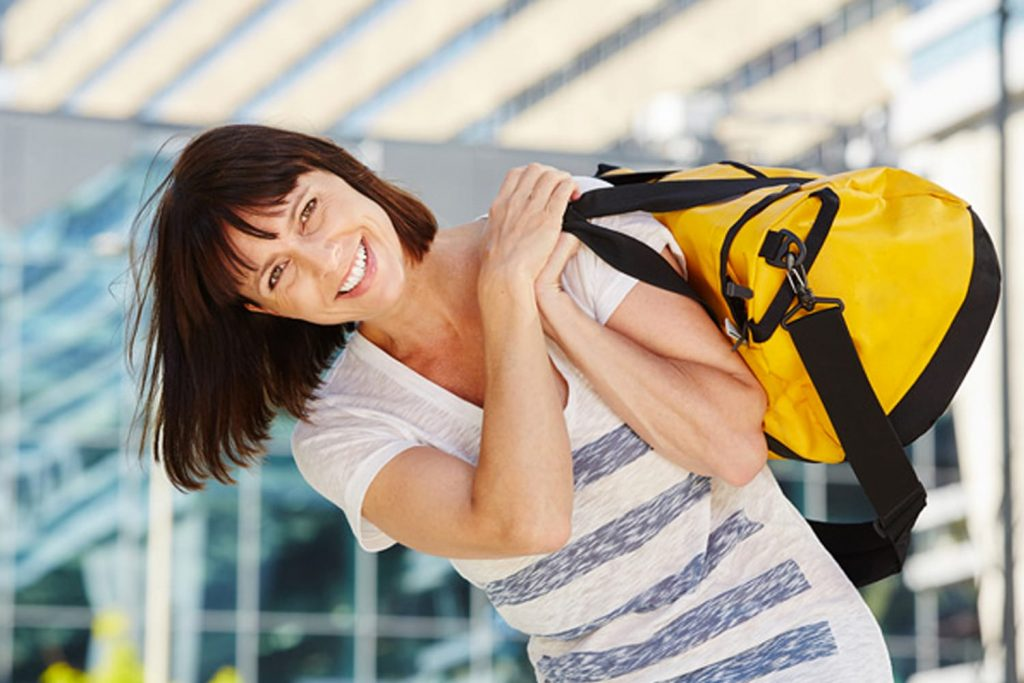 Portrait of happy traveler carrying duffel bag over shoulder