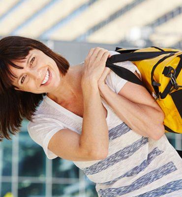 Portrait of happy traveler carrying duffel bag over shoulder