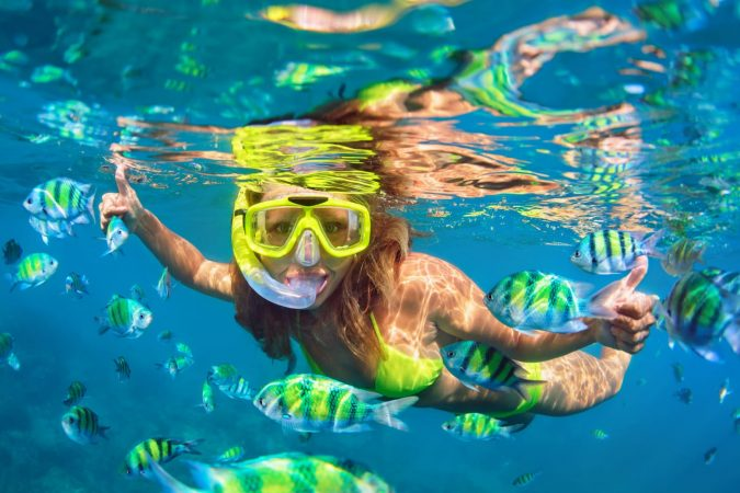 girl in snorkeling mask dive underwater with fishes