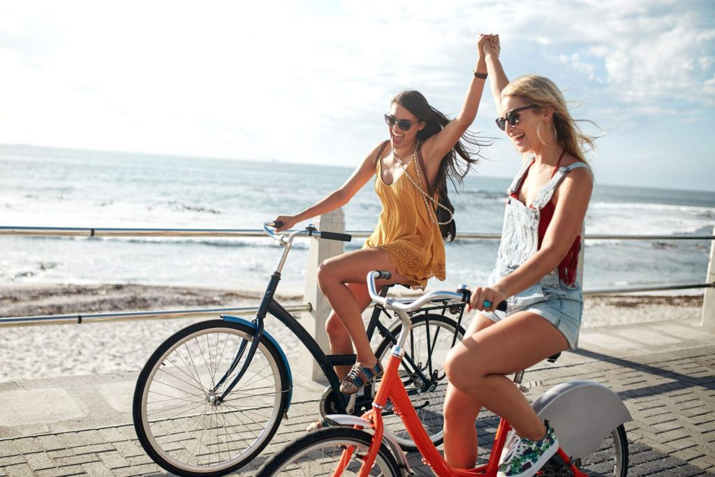 Female friends enjoying cycling on a summer day. Two young female friends riding their bicycles on the seaside promenade.