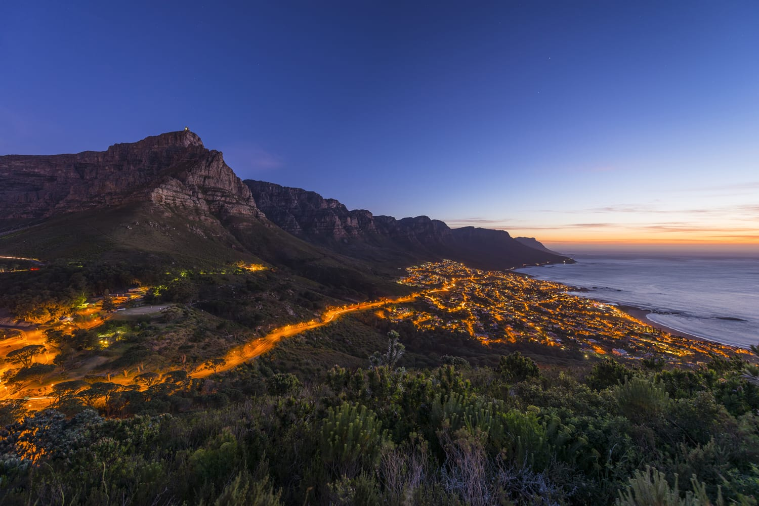 Cape Town's Table Mountain & Twelve Apostles seen from Lions Head hiking peak & Twelve Apostles with camps bay suburb and ocean below