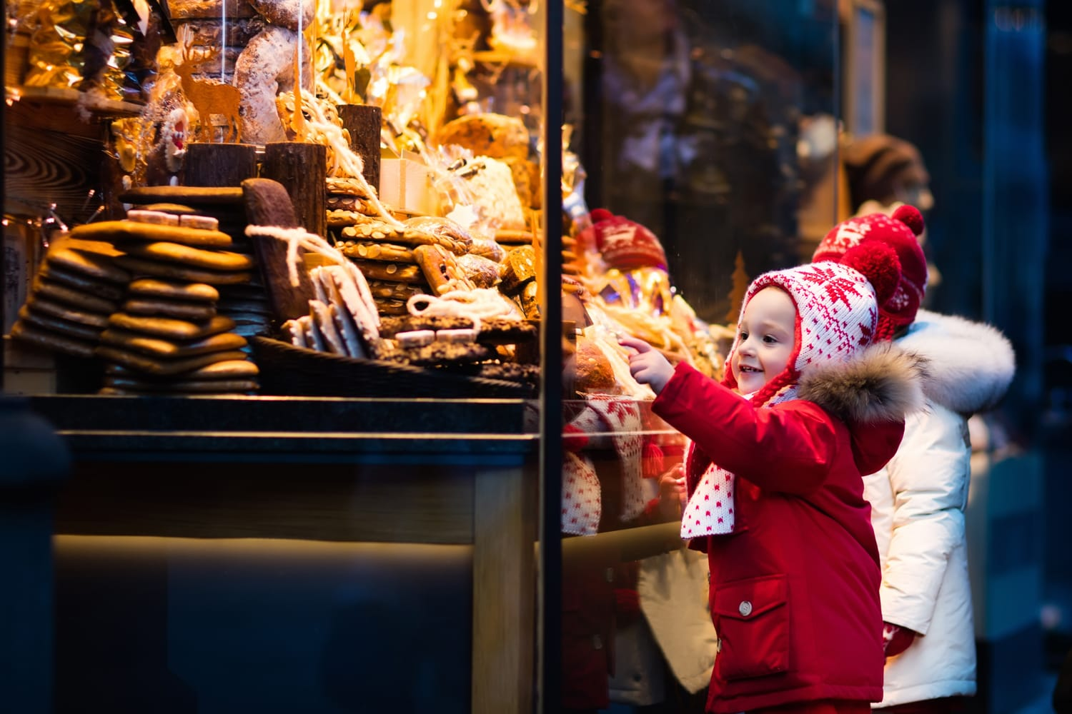 Children window shopping on traditional Christmas market in Germany on snowy winter day
