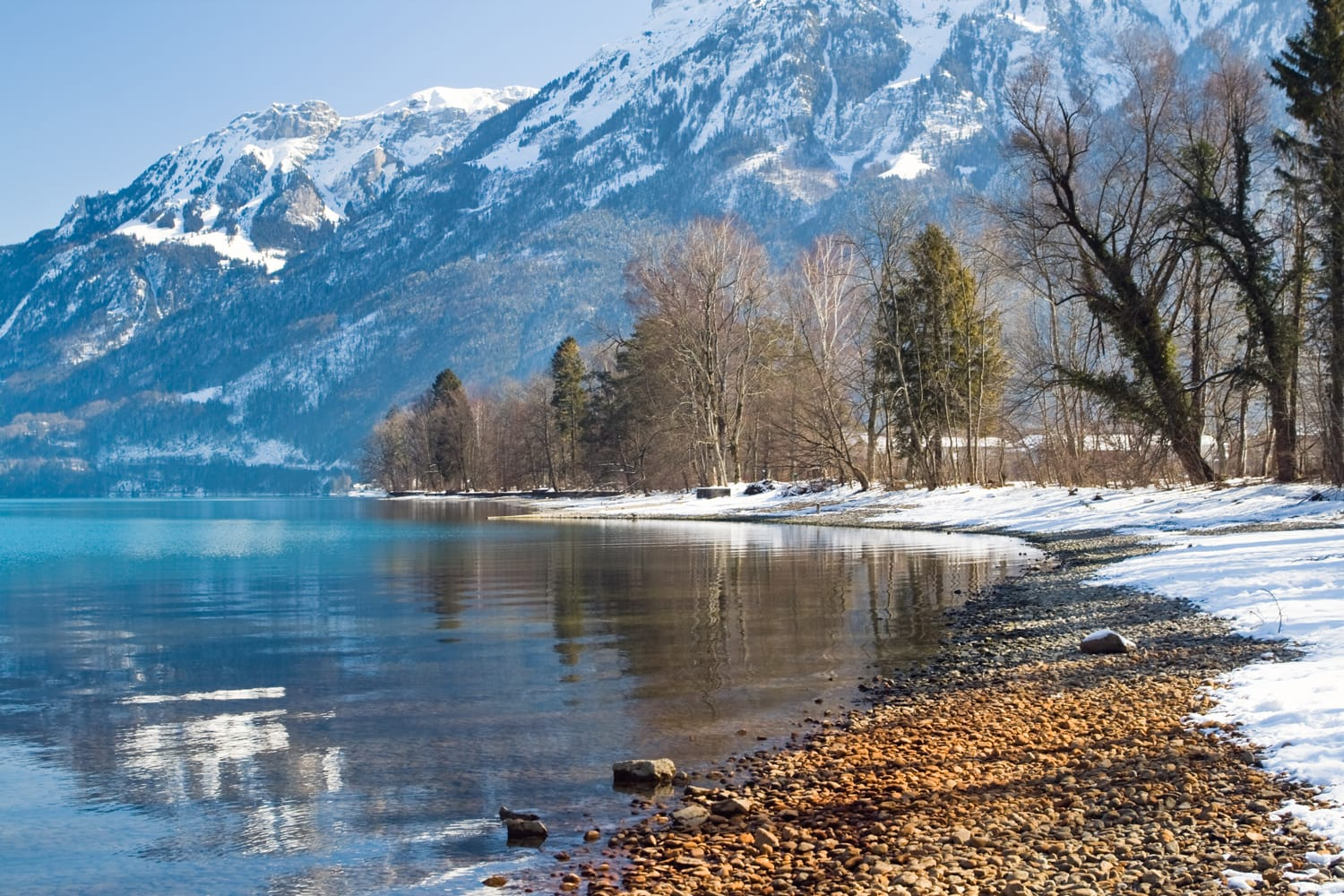 Horizontal image of the lake reflection on shore in the Alps with a blue background, Interlaken, Swiss.
