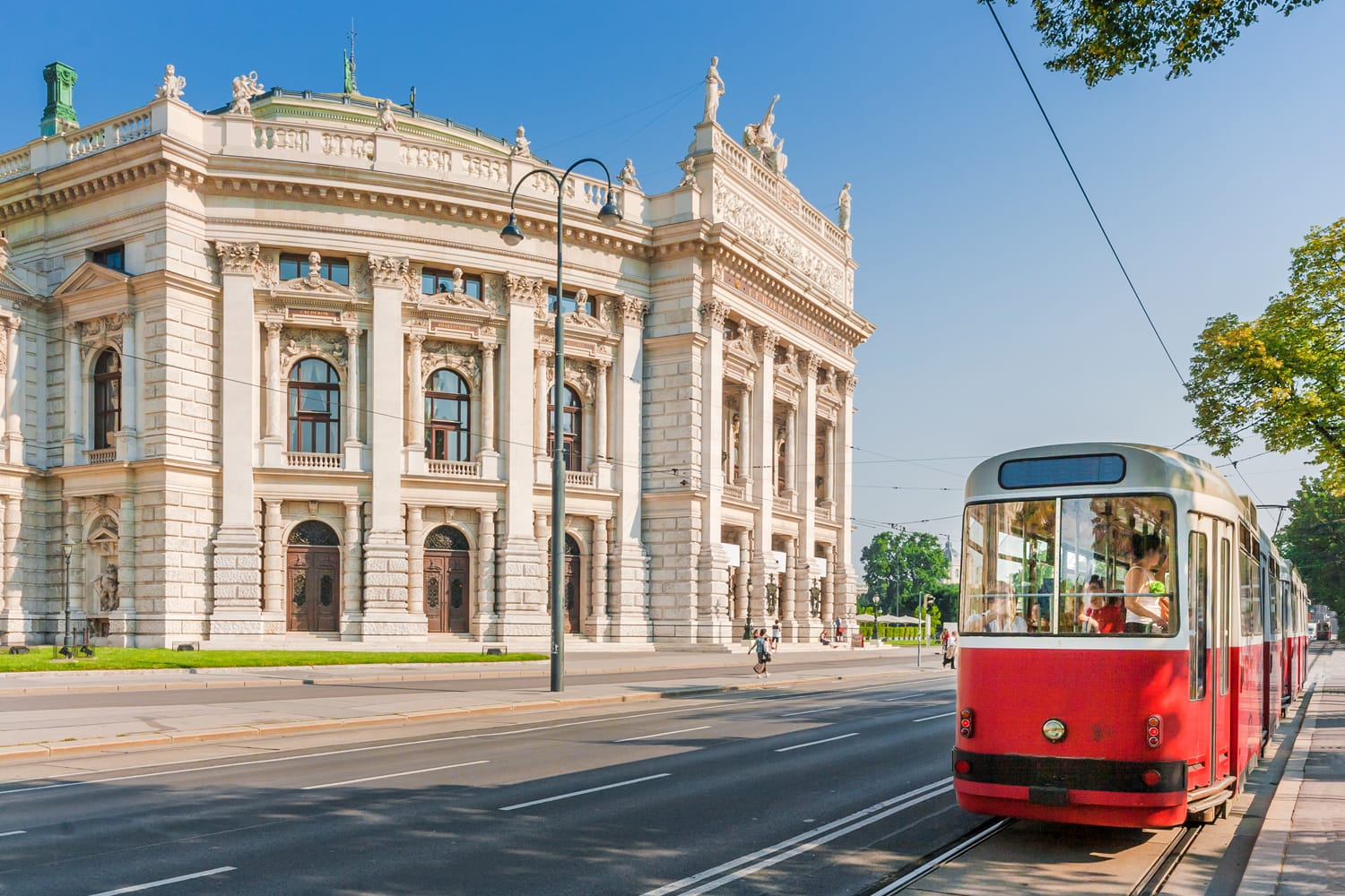 Famous Wiener Ringstrasse with historic Burgtheater (Imperial Court Theatre) and traditional red electric tram at sunset in Vienna, Austria