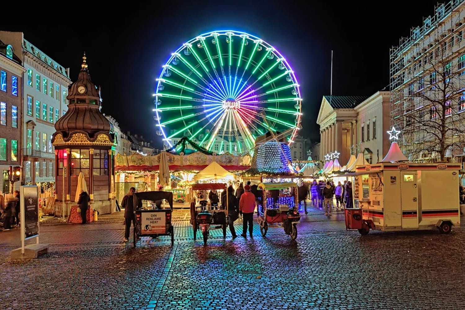 Christmas market with Ferris wheel on the Nytorv square in evening