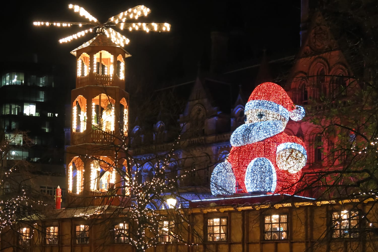 Santa Claus on Christmas market and town hall on Albert Square in Manchester at night.