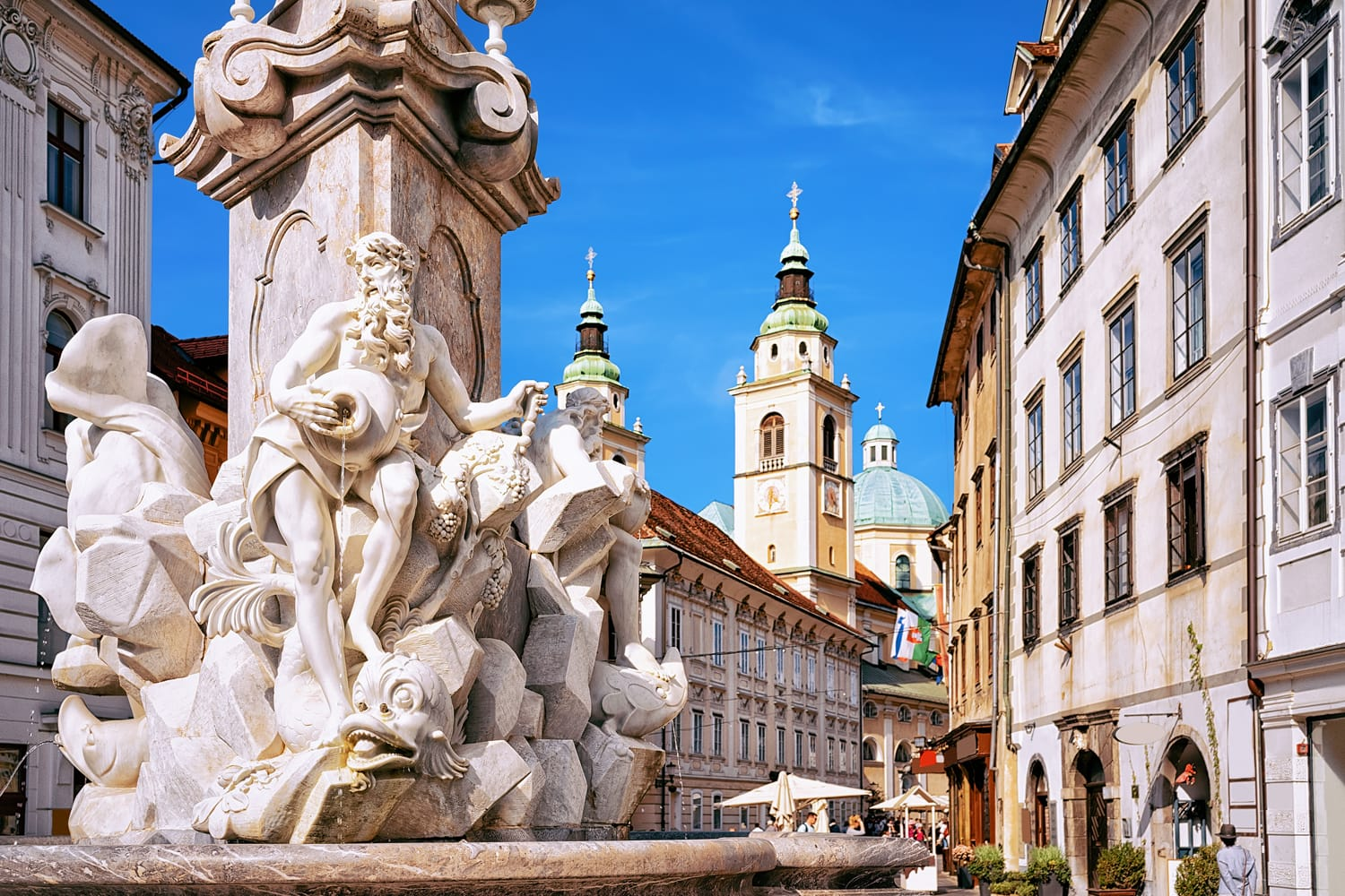 Fragment of Robba fountain in the historical center of Ljubljana, Slovenia. Ljubljana Cathedral on the background