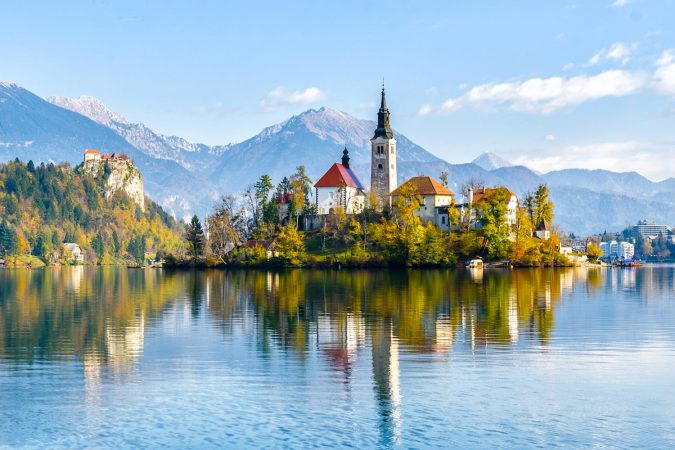 Lake Bled Slovenia. Beautiful mountain lake with small Pilgrimage Church. Most famous Slovenian lake and island Bled with Pilgrimage Church of the Assumption of Maria and Bled Castle in background.