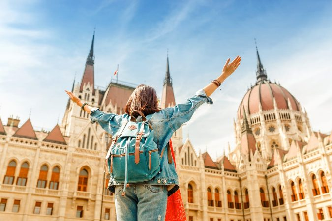 Happy asian casual woman student enjoying great view of the Parliament building in Budapest, Hungary
