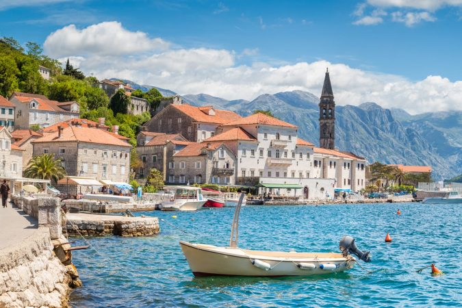 Scenic panorama view of the historic town of Perast located at world-famous Bay of Kotor on a beautiful sunny day with blue sky and clouds in summer, Montenegro