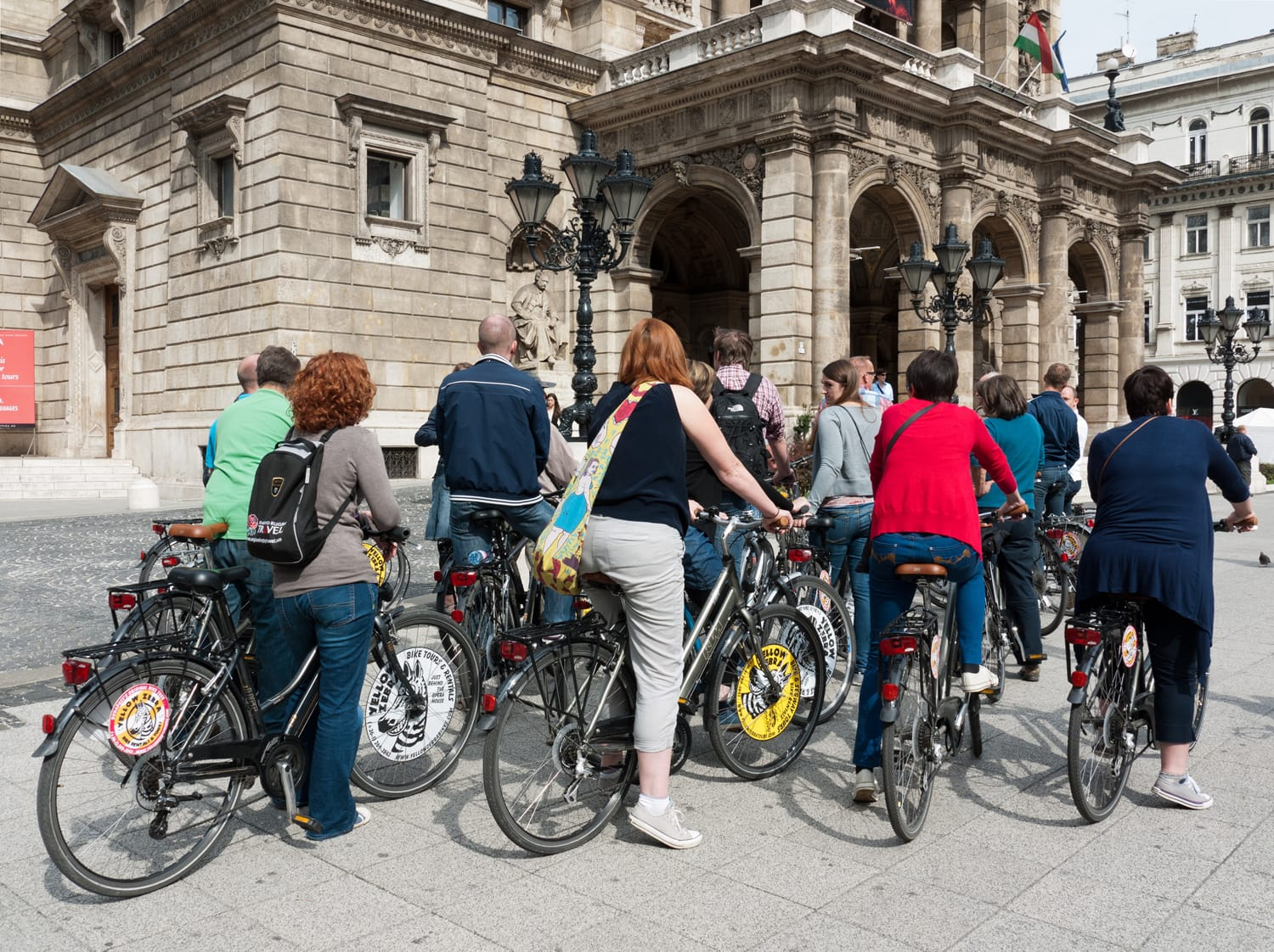 Tourists on rented bikes in front of the Opera House on Andrassy Avenue in Budapest, Hungary