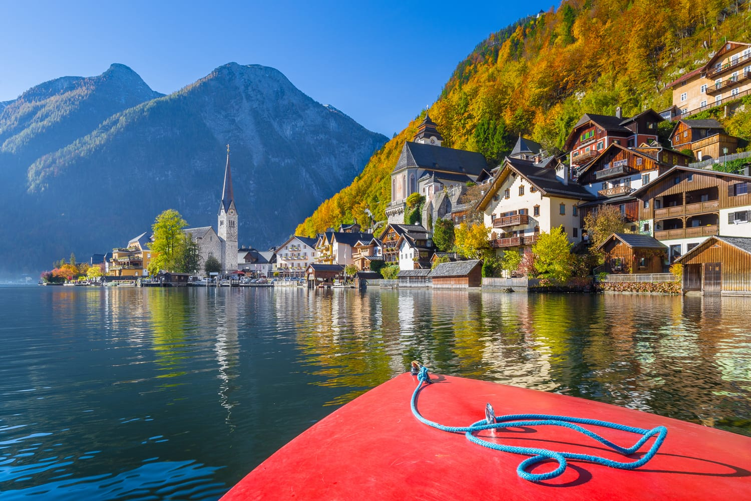 Scenic picture-postcard view of famous Hallstatt mountain village during a boat tour on Hallstatter See in the Austrian Alps in beautiful golden morning light in fall, region of Salzkammergut, Austria