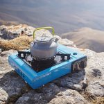 Portable camping gas stove with a gray kettle on a background of nature in the mountains.