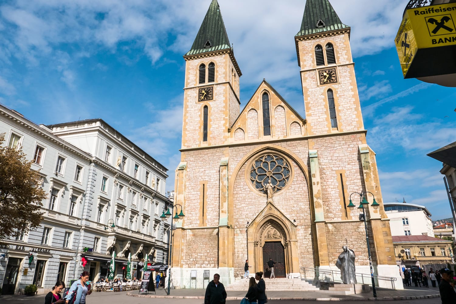 The Cathedral of Jesus' Sacred Heart in Sarajevo, Bosnia and Herzegovina, on a sunny day with people in the street