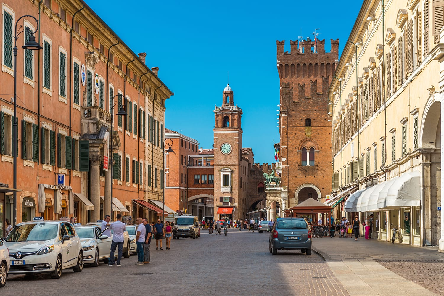 Central street of Ferrara. Taxi cabs and drivers near them. People walking in the historical part of the city