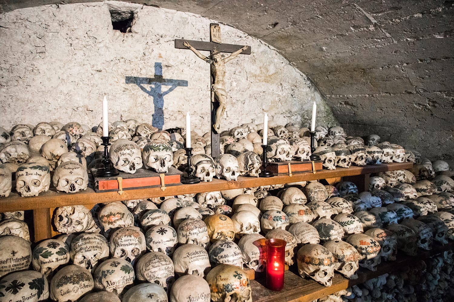 Skulls painted with names, colorful flowers and crosses in the Charnel House or Beinhaus, Hallstatt, Austria