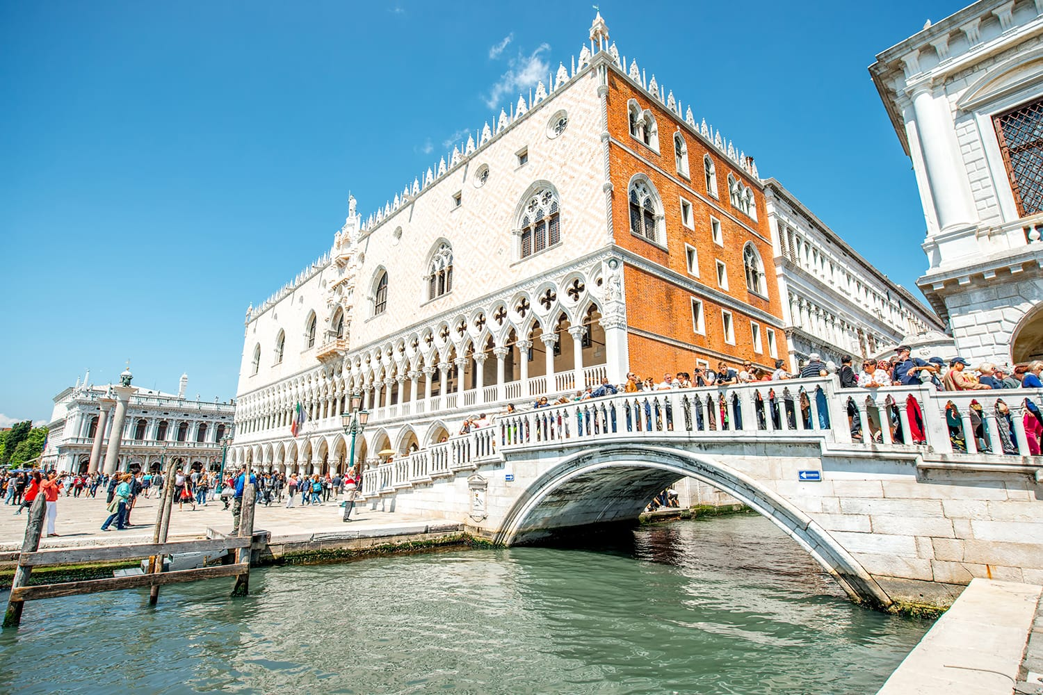 View on Doges palace with tourists walk on the bridge and San Marco square in Venice, Italy