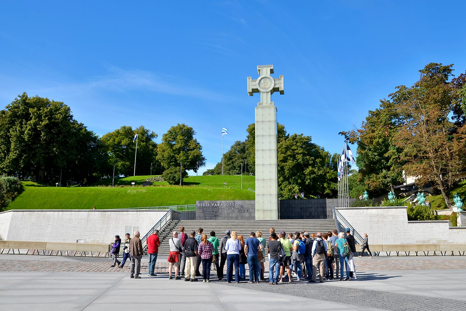 Tourists visiting Freedom Square, the War of Independence Victory Column in Tallinn, Estonia