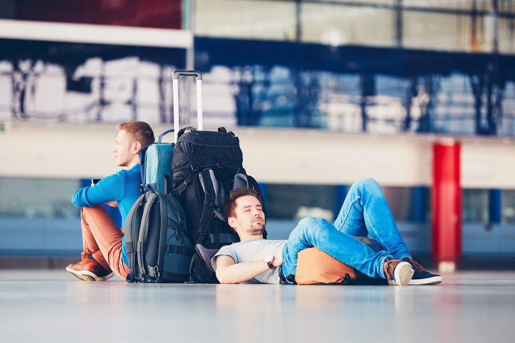 Two friends traveling together. Travelers waiting at the airport departure area for their delay flight