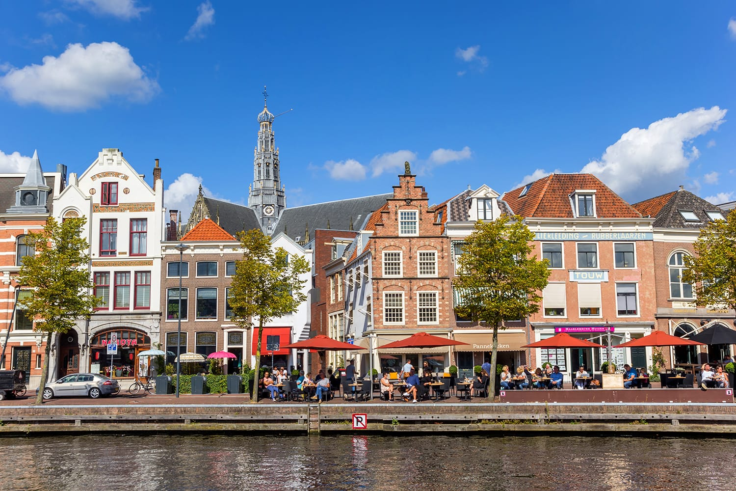 People enjoying the sun at a historic canal in Haarlem, Netherlands