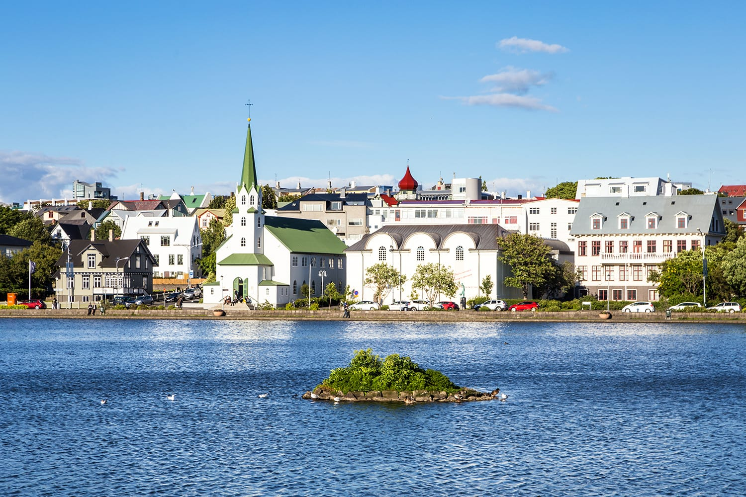 Reykjavik cityscape viewed from across the Tjornin lake in the heart of Iceland capital city on a sunny summer day.