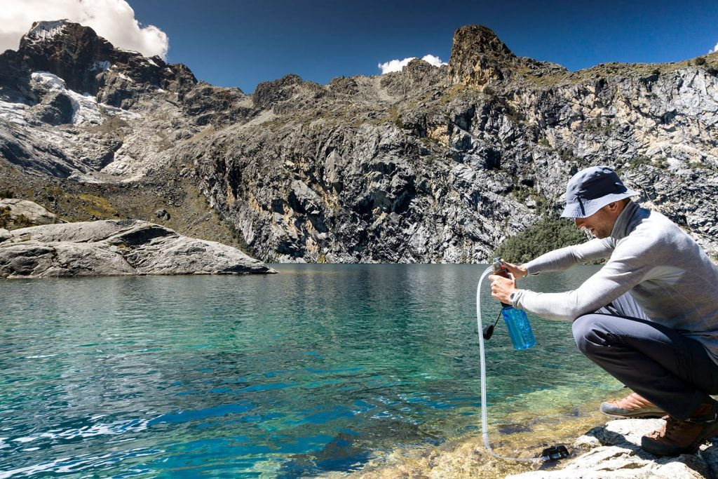 oung mountain climber filtering and pumping water for drinking from a turquoise mountain lake high up in the Peruvian Andes