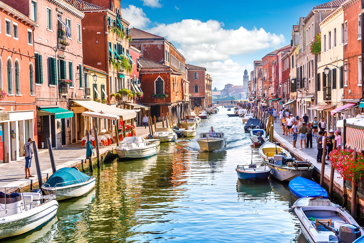 Island murano in Venice Italy. View on canal with boat and motorboat water.