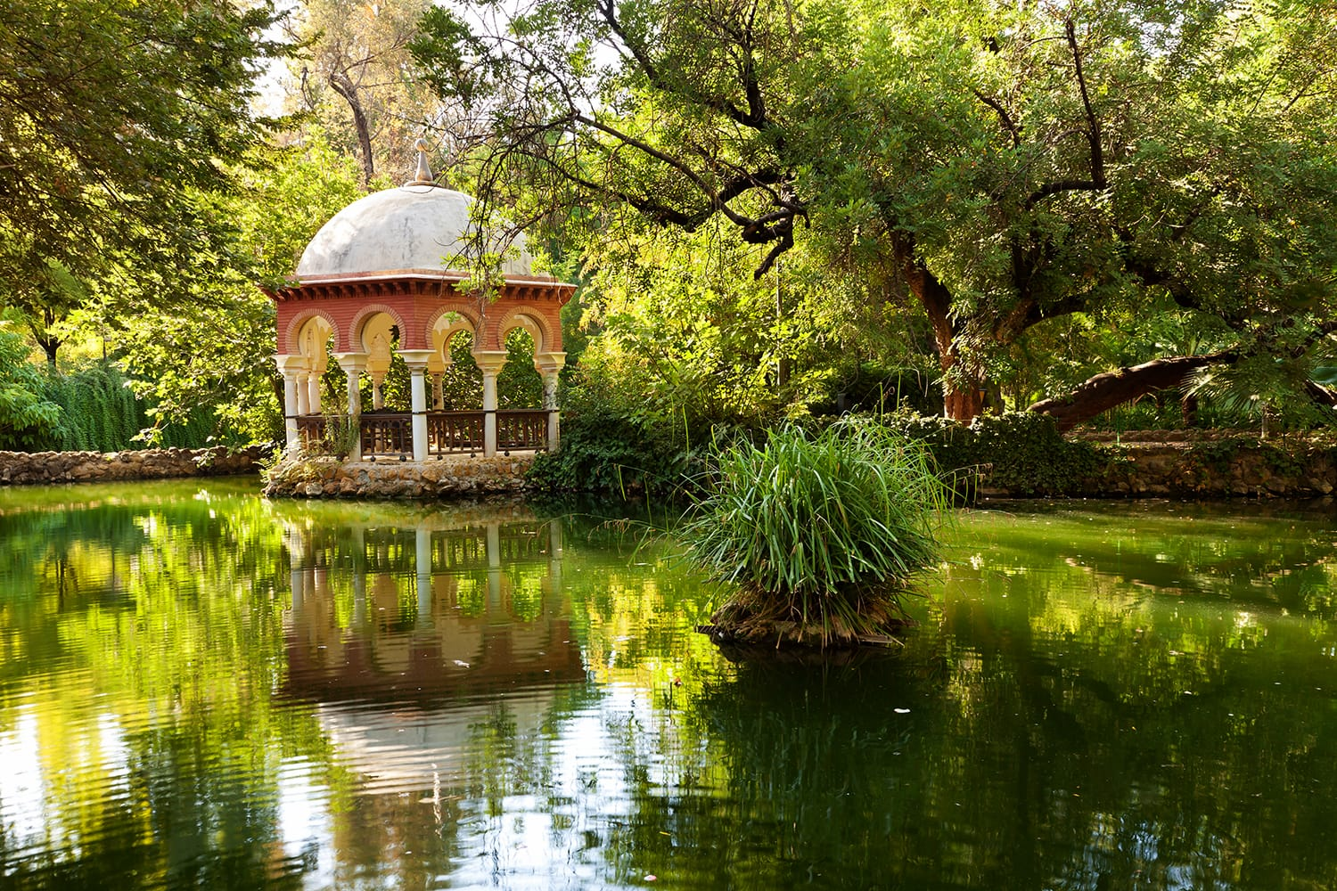 Romantic pavilion reflected in a pond. Parque Maria Luisa of Sevilla, Spain