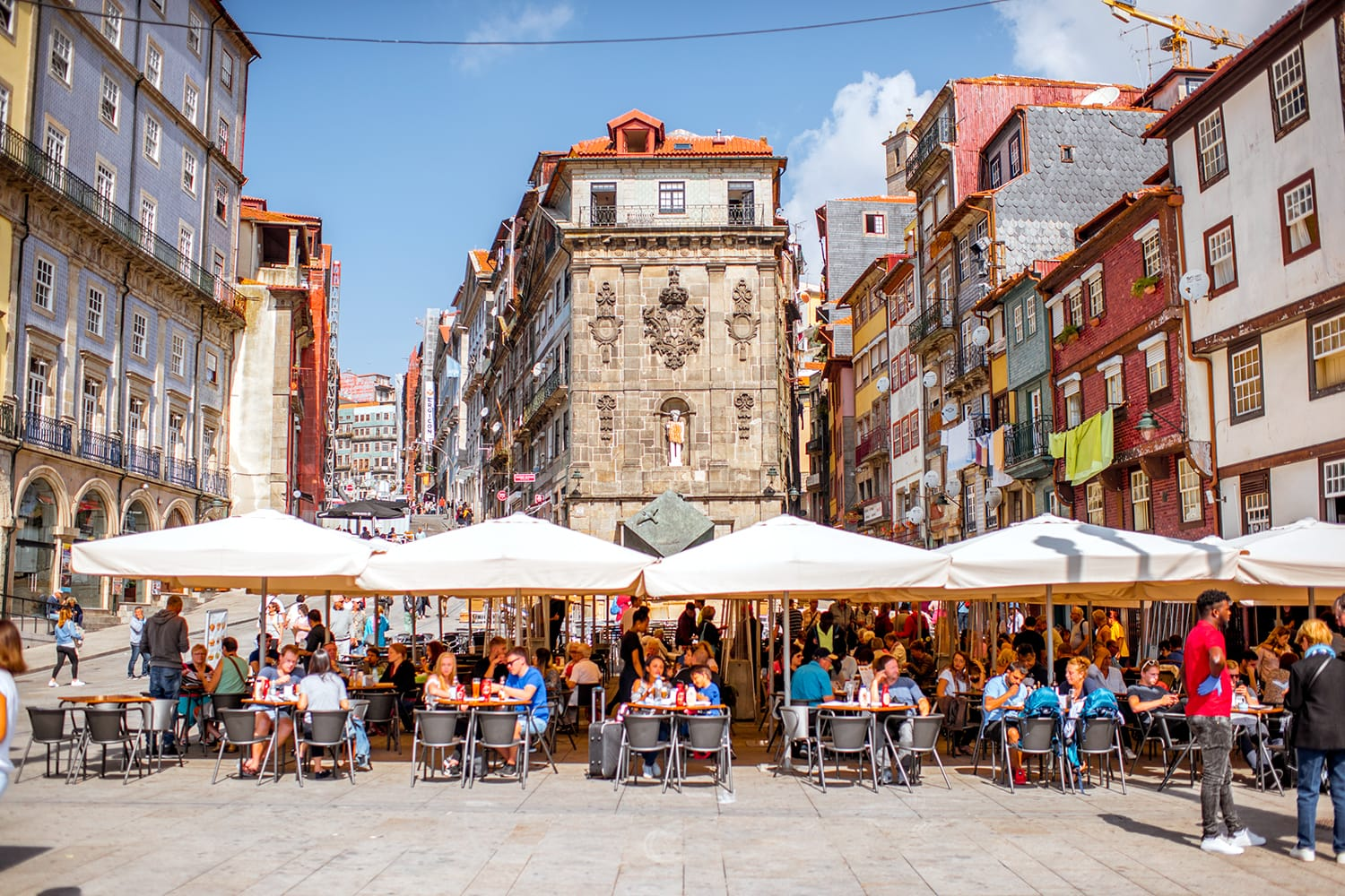 View on the Ribeira square with tourists sitting at the bars and restaurants in Porto city, Portugal
