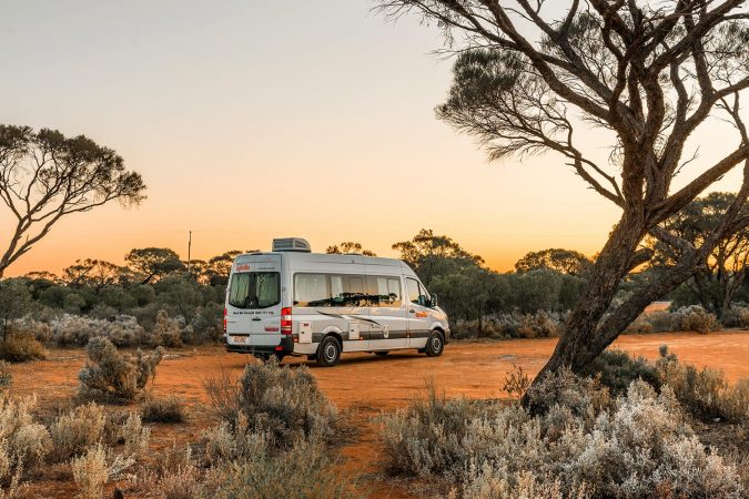 Australian rented motorhome stopped in at bush campgroung in Flinders Ranges region near Port Augusta at sunset. Australia