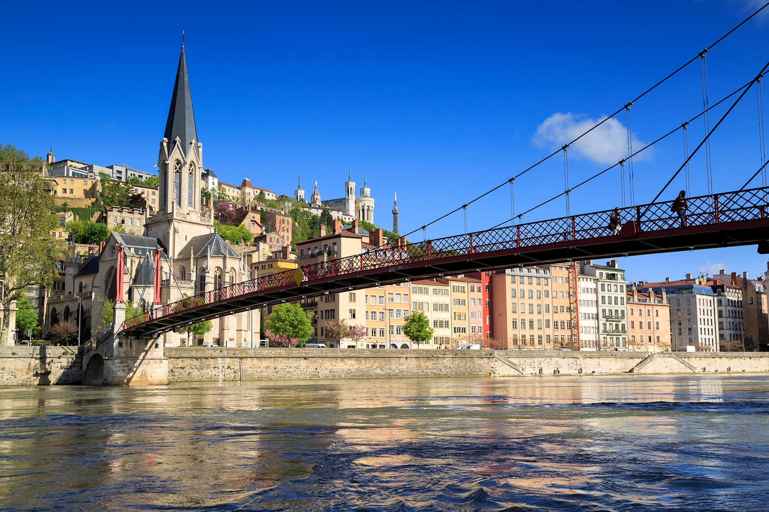 Pedestrians on the Saint Georges footbridge and the Saint Georges church in Lyon, France